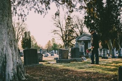 man brings flowers to a cemetery memorial